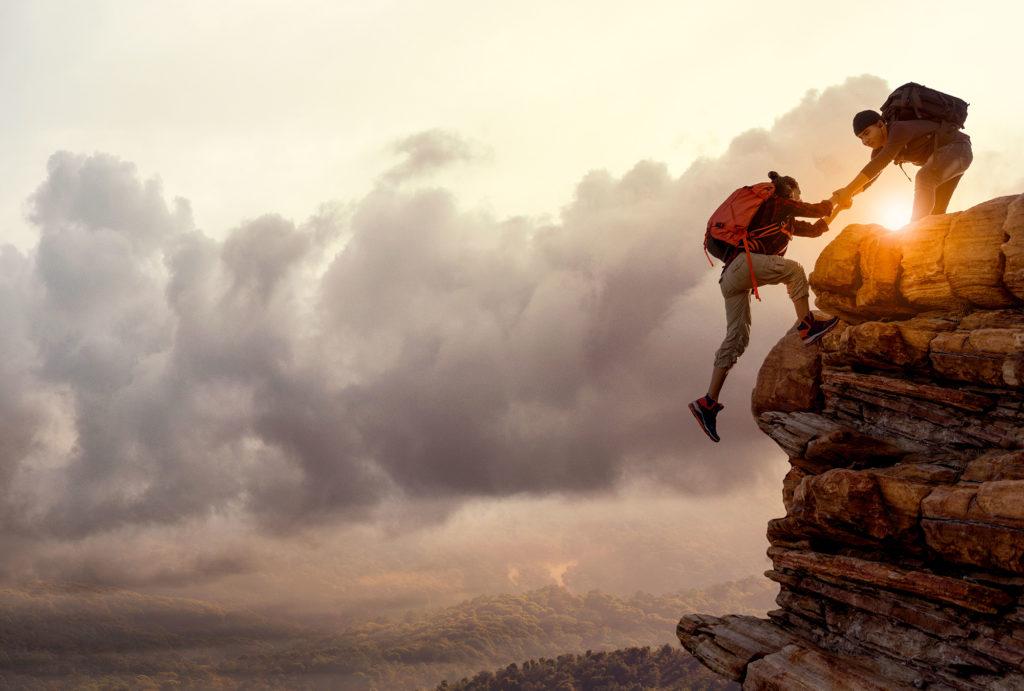 persona-aiuta-altra-persona-a-scalare-montagna