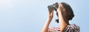 donna-guarda-lontanto-con-binocolo